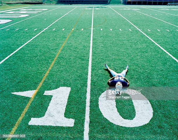 Football player stetching on 10 yard line, elevated view