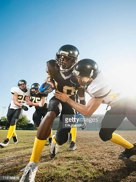 football player tackling player on football field - safety american football player stock pictures, royalty-free photos & images