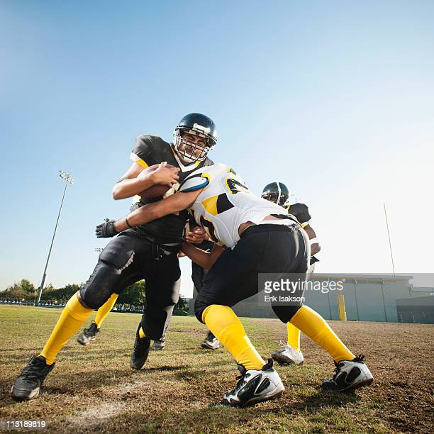 football player tackling player on football field - tackling stock pictures, royalty-free photos & images