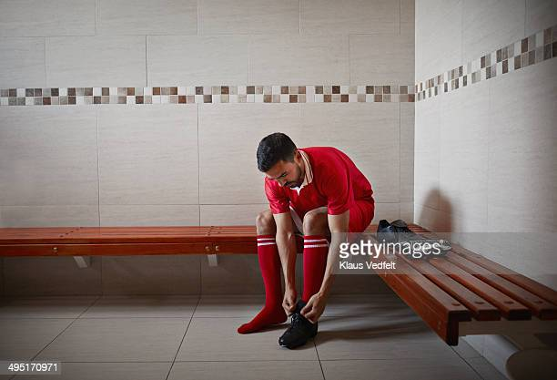 football player tying shoe, alone in changing room - locker room stock pictures, royalty-free photos & images