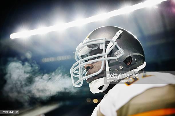 Football player wearing helmet standing on field