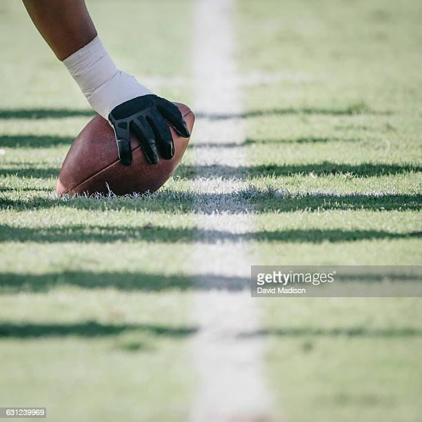 football player with hand on ball - snapping the ball stock pictures, royalty-free photos & images