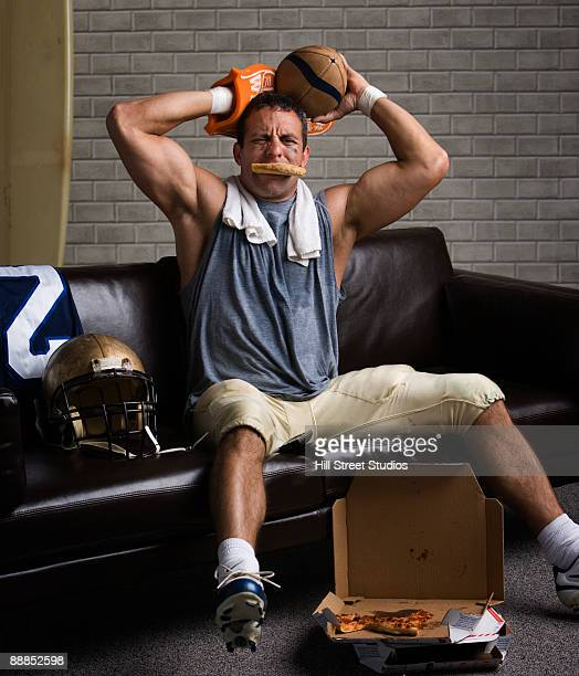 football player with pizza in mouth looking frustrated - foam finger stock photos and pictures