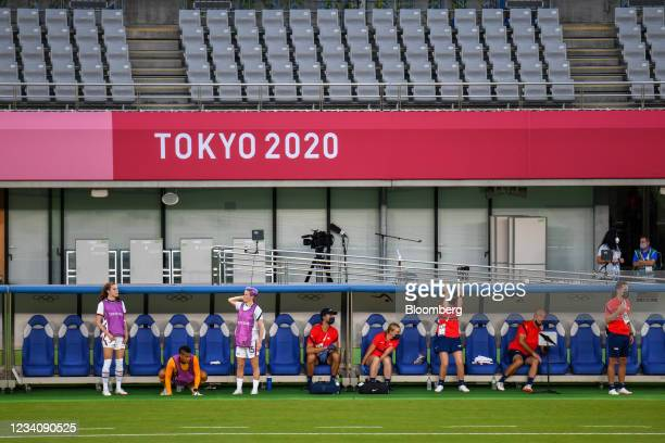 Football players and coaching staff watch from the bench area during an opening round women's football match between the U.S. And Sweden at the Tokyo...
