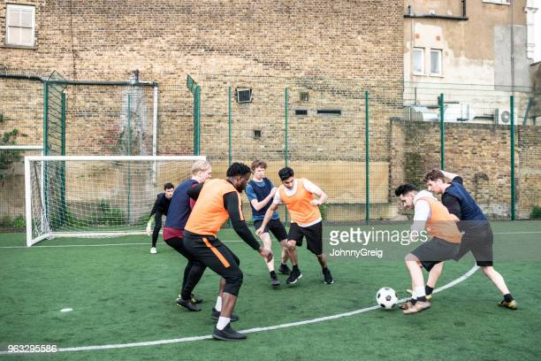 Football players approaching the goal with young man tackling his opponent