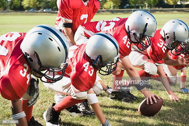 football players at line of scrimmage ready to snap football - center athlete stock pictures, royalty-free photos & images