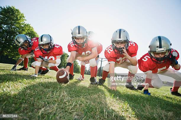 football players at line of scrimmage ready to snap football - sports activity stock pictures, royalty-free photos & images
