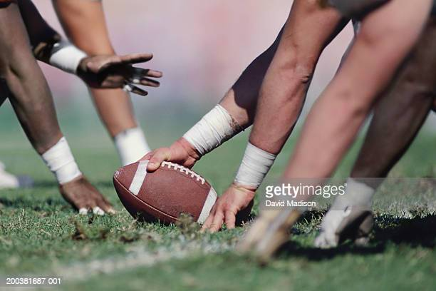 football players at line of scrimmage, side view (focus on football) - line of scrimmage stock pictures, royalty-free photos & images