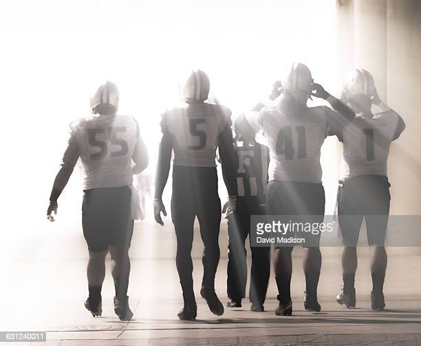 football players enter stadium. - safety american football player stock pictures, royalty-free photos & images