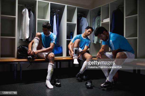 football players getting ready in locker room. - umkleideraum stock-fotos und bilder