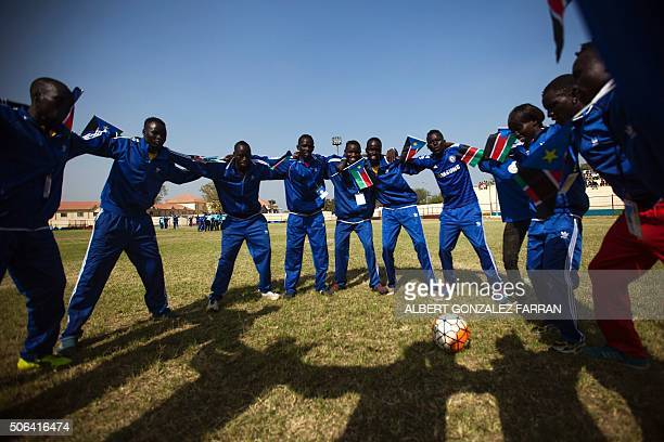 TOPSHOT Football players holding South Sudanese flags make a circle at the Juba Stadium during the closing ceremony of the National Unity Day events...