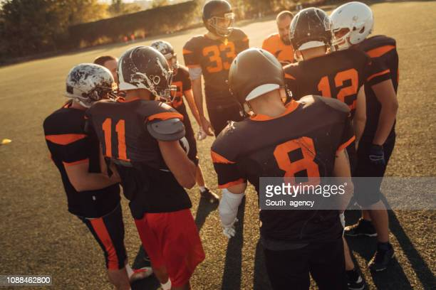 football players huddling - american football team stock pictures, royalty-free photos & images