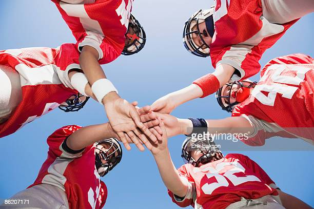 Football players joining hands in huddle