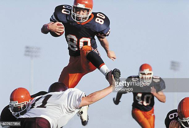 Football Players Leaping Over Defenders