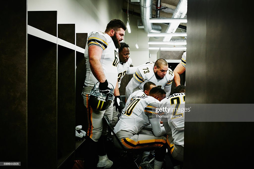 Football players listening to coach in locker room : Stock Photo