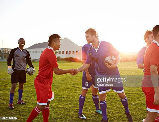 Football players making handshake after match