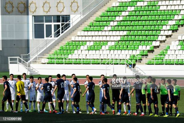 Football players of Altyn Asyr greet Kopetdag's one prior to the Turkmenistan national football championship match between Altyn Asyr and Kopetdag on...