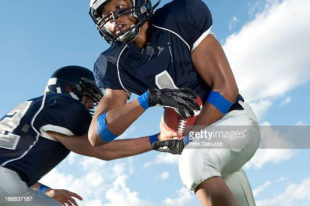 football players passing ball - high school football stock pictures, royalty-free photos & images