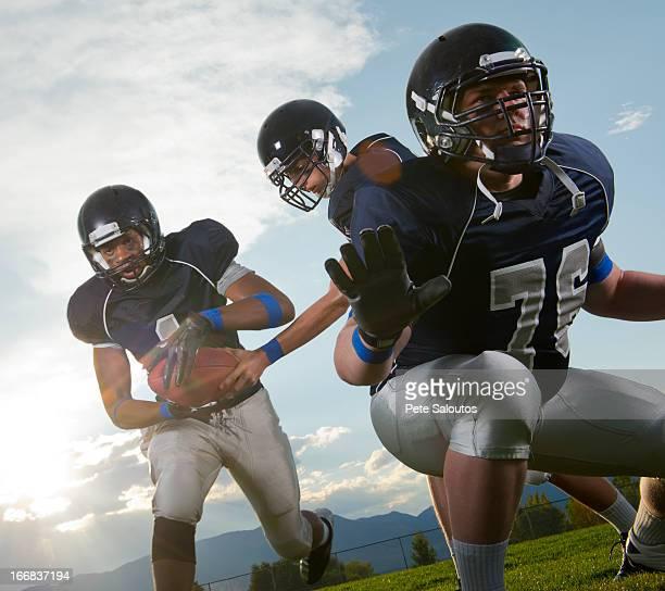 Football players passing ball