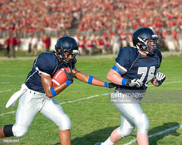 football players passing ball - safety american football player stock pictures, royalty-free photos & images