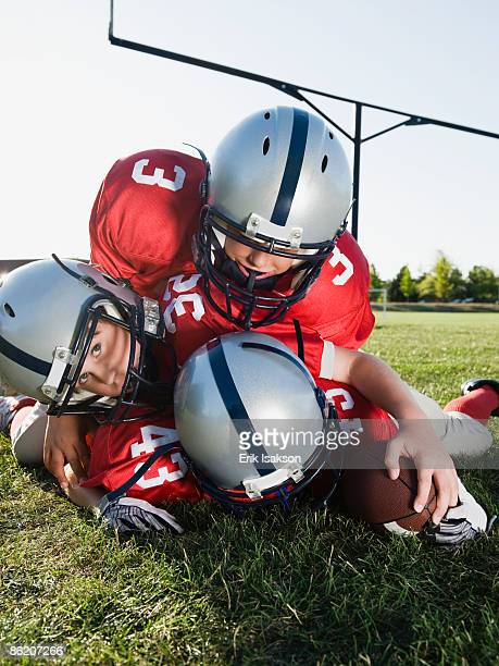 football players piled on ball - tackling stock pictures, royalty-free photos & images