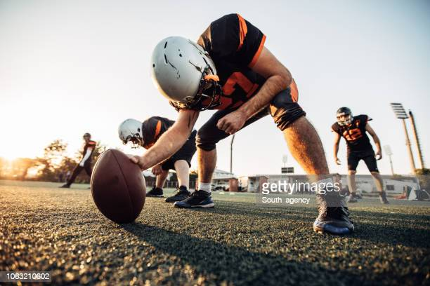 football players playing a match on a field - quarterback stock pictures, royalty-free photos & images
