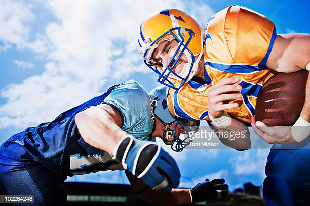 football players playing football - tackling stock pictures, royalty-free photos & images