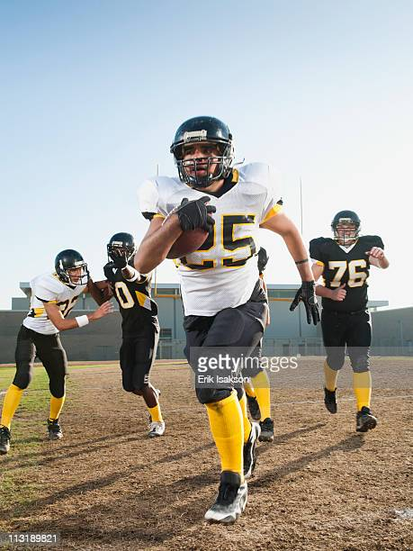 football players playing on football field - safety american football player stock pictures, royalty-free photos & images