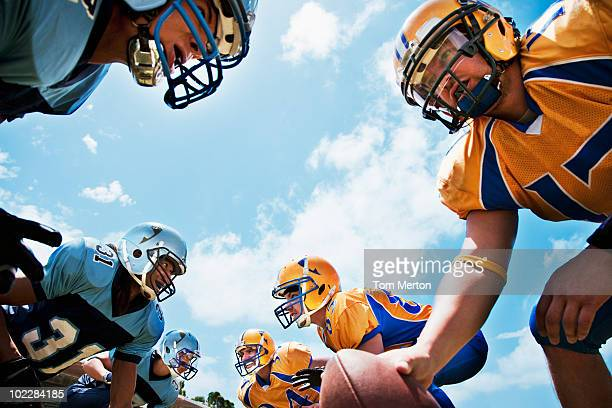 football players preparing to play football - face off sports play stock photos and pictures