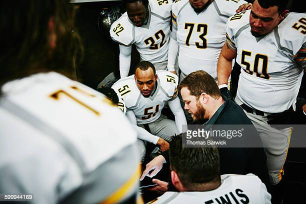 Football players reviewing play with coach
