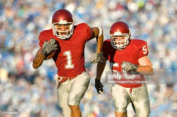 football players running on field in game - rush american football stock pictures, royalty-free photos & images