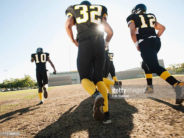 football players running on football field - safety american football player stock pictures, royalty-free photos & images