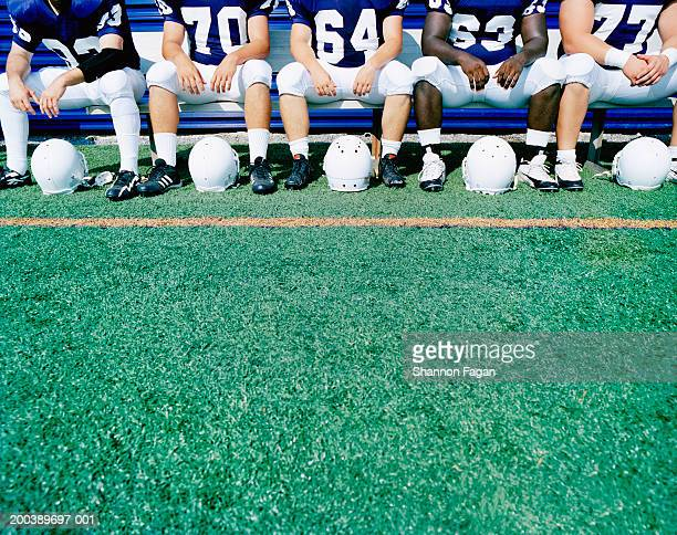 Football players sitting on bench, mid section