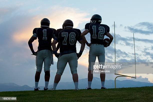 football players standing on field - safety american football player stock pictures, royalty-free photos & images