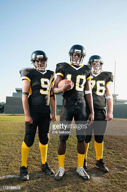 football players standing on football field - safety american football player stock pictures, royalty-free photos & images