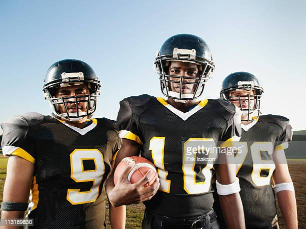 football players standing on football field - high school football stock pictures, royalty-free photos & images