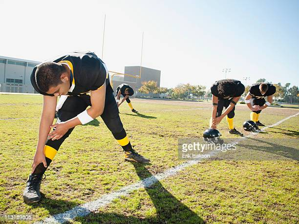 football players stretching on football field - high school football stock pictures, royalty-free photos & images