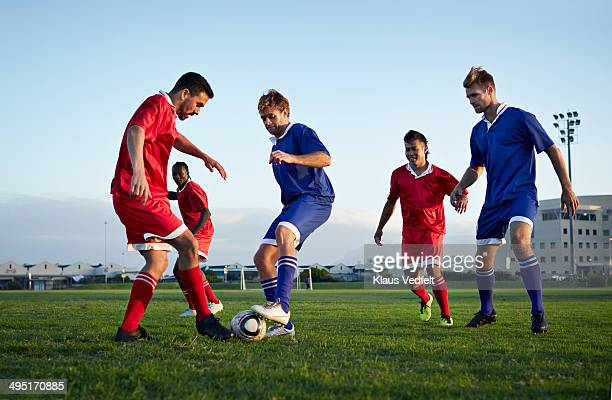 football players tackling the ball on the field - match sportivo foto e immagini stock