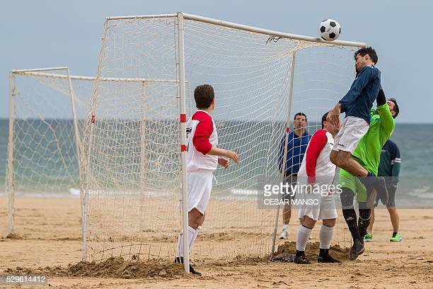Football players vie during the 52nd Football Championship Santander beach football amateur match on the beach of the Sardinero of Santander northern...