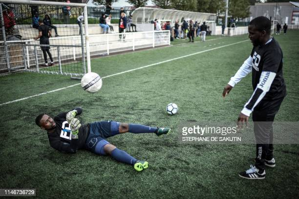"""Football players warm up prior a match between 'Mali' and 'the rest of the world' teams as part of the """"CAN Epinetzo"""", an amateur football tournament..."""