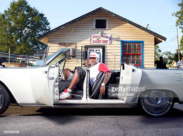 Portrait of former Oakland Raiders QB JaMarcus Russell seated with his father in his Lincoln Continental outside of the Maysville Barber Shop Mobile...