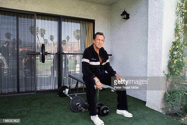 Portrait of Oakland Raiders owner Al Davis lifting weights during photo shoot at temporary offices after signing a Memorandum of Agreement to move...