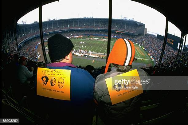 Rear view of Cleveland Browns fans in stands with signs that depict the Three Stooges Larry Curly and Modell One sign has Modell saying I'D SELL MY...