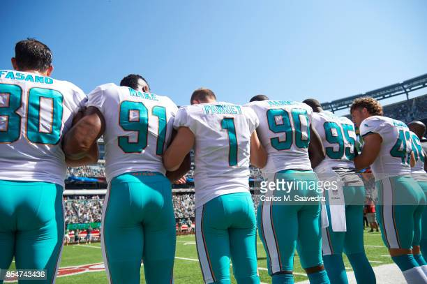 Rear view of Miami Dolphins Anthony Fasano Cameron Wake Cody Parkey Charles Harris William Hayes and Alterraun Verner link arms in solidarity during...