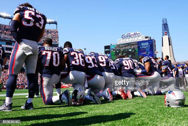 Rear view of New England Patriots players kneeling on sidelines with arms linked during National Anthem before game vs Houston Texans at Gillette...