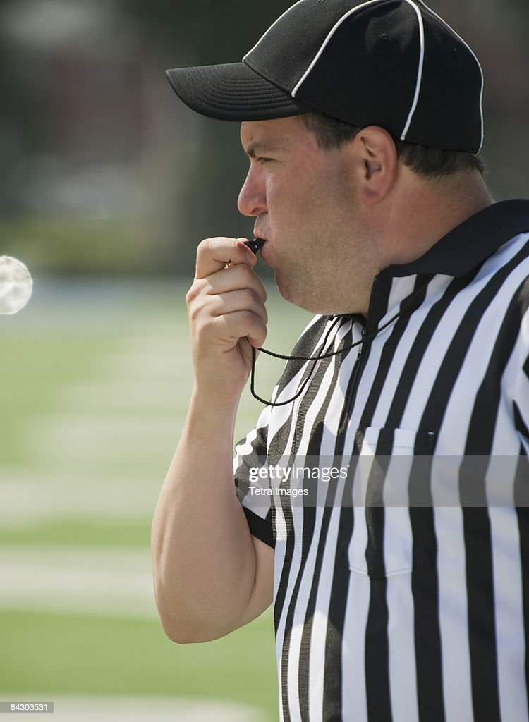 Football referee blowing whistle : Stock Photo