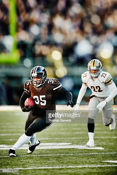 football running back carrying ball downfield - rush american football stock pictures, royalty-free photos & images