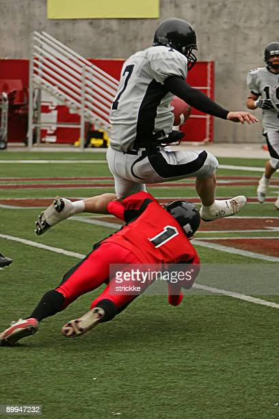 football running back hurdles defender for touchdown - tackling stock pictures, royalty-free photos & images