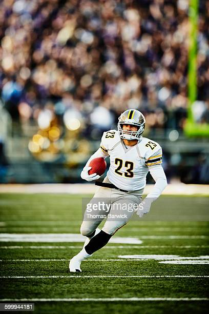 football running back with ball running downfield - american football player stock pictures, royalty-free photos & images