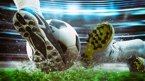 Football scene at night match with close up of a soccer shoe hitting the ball with power 1171170426